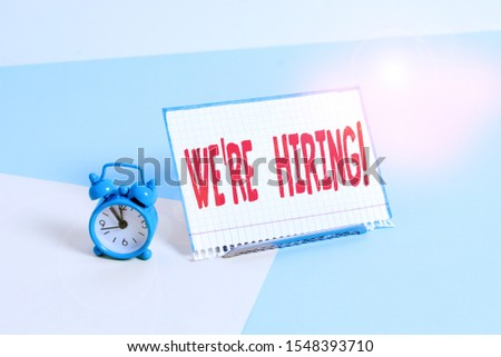 Word writing text We Re Hiring. Business concept for recently employ someone or pay him to do particular job Mini size alarm clock beside a Paper sheet placed tilted on pastel backdrop.