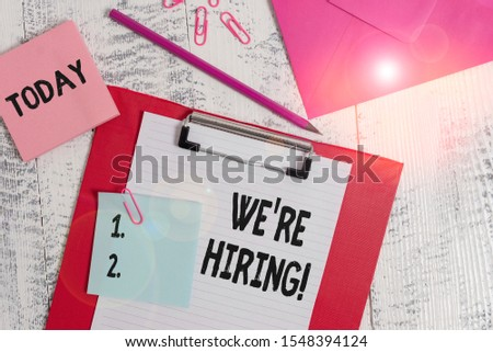 Word writing text We Re Hiring. Business concept for recently employ someone or pay him to do particular job Clipboard paper sheet pencil note envelope clips notepad wooden background.