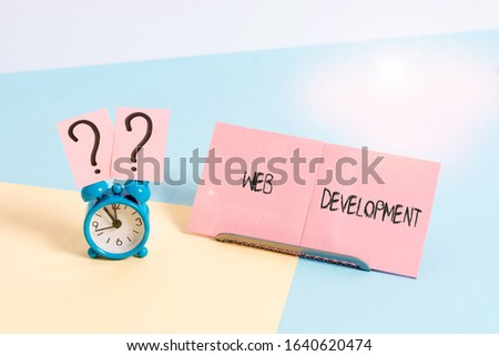 Word writing text Web Development. Business concept for dealing with developing websites for hosting via intranet Mini size alarm clock beside a Paper sheet placed tilted on pastel backdrop.
