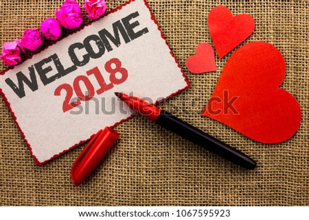 Word writing text Welcome 2018. Business concept for Celebration New Celebrate Future Wishes Gratifying Wish written on Cardboard Piece on the jute background Marker and Hearts next to it. #1067595923