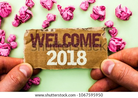 Word writing text Welcome 2018. Business concept for Celebration New Celebrate Future Wishes Gratifying Wish written on Tear Cardboard Piece Holding by Man on the plain background. #1067595950