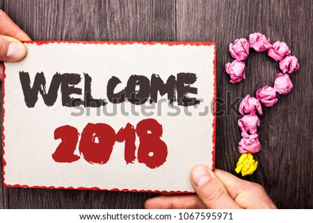 Word writing text Welcome 2018. Business concept for Celebration New Celebrate Future Wishes Gratifying Wish written on Cardboard Piece Holding By Hand on wooden background Question Mark. #1067595971