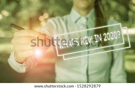 Word writing text What S New In 2020 Question. Business concept for Expectation and Surprises for the coming Year Woman in a blue business shirts pointing with her finger into empty space.