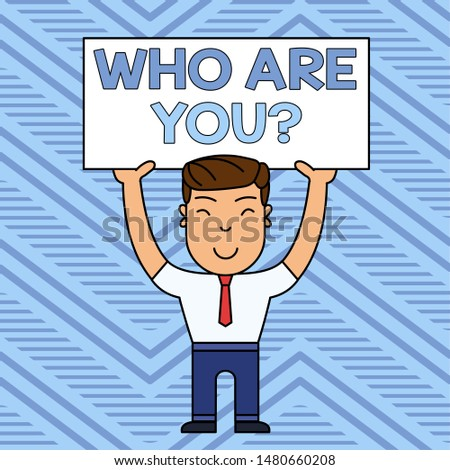 Word writing text Who Are You Question. Business concept for asking about someone identity or demonstratingal information Smiling Man Standing Holding Big Empty Placard Overhead with Both Hands.