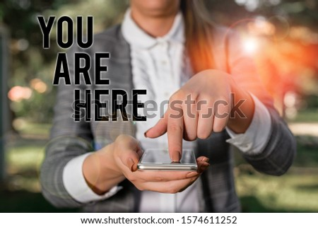 Word writing text You Are Here. Business concept for This is your location reference point global positioning system Woman in grey suites holds mobile phone. #1574611252