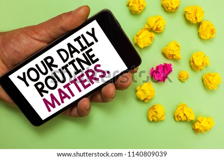Word writing text Your Daily Routine Matters. Business concept for Have good habits to live a healthy life Man holding cell phone white screen looking messages crumpled papers.