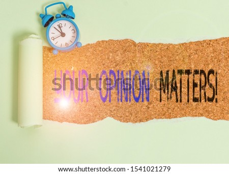 Word writing text Your Opinion Matters. Business concept for show you do not agree with something that just been said Alarm clock and torn cardboard placed above a wooden classic table backdrop.