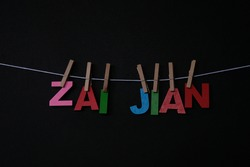 Word Zai Jian on black background. Zai Jian means good bye in Chinese . Concept for art, learning, and education.