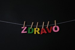 Word Zdravo on black background. Zdravo means good bye in Serbian. Concept for art, learning, and education.