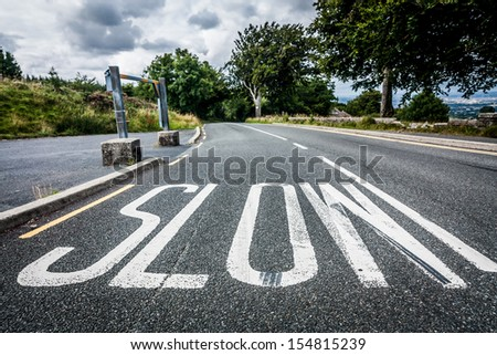 Worded marking  SLOW painted on the road to warn drivers to slow down