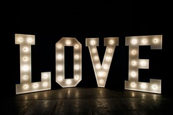 Wording Love sign with light bulb isolate on black background