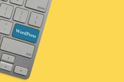WORDPRESS text on keyboard over yellow background. Business and technology concept