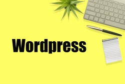 WORDPRESS text with Flat lay, top view office table desk. Workspace with pen, notepad, decoration plant and keyboard on the yellow background