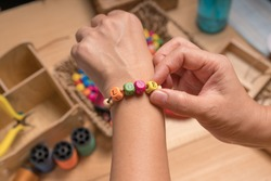 Words concept, String a bracelet Wooden letter beads of LOVE word. Close up woman hand string color Wooden letter beads.