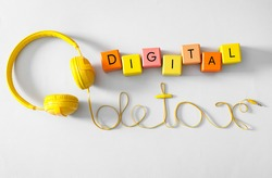 Words DIGITAL DETOX made with colorful cubes and wire of headphones on white background, top view
