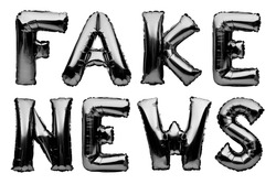 Words FAKE NEWS made of black inflatable balloons isolated on white background. Helium balloons black foil forming phrase fake news. Event concept, false information.