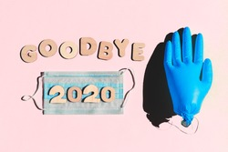 Words GOODBYE 2020 from wooden letters, inflated medical glove waving bye-bye and facemask on a pink background. Year 2020 and epidemic concept.