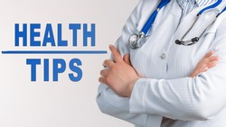 Words - Health Tips on a white background. Nearby is a doctor in white coat and stethoscope. Medical concept