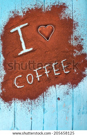 Words i love coffee written on ground coffee, coffee powder on blue wooden table