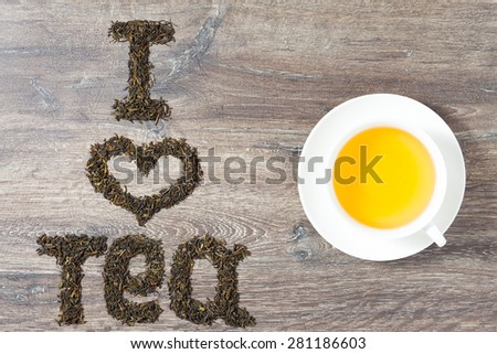 Words I love tea made of green tea leaves on wood background. Text on the left. A cup of tea on the right