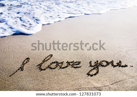 "words ""I love you"" outline on the wet sand with the wave brilliance"