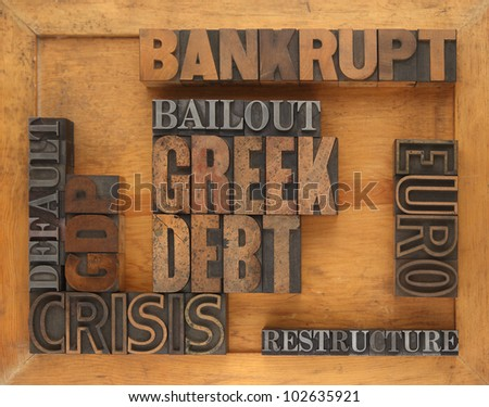 words in letterpress wood and metal type having to do with the Greek debt situation