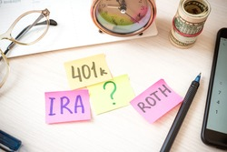 Words 401k ira roth on pieces of colorful paper, money dollars and glasses on table. Pension concept. Retirement plans.