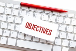 Words OBJECTIVES written on torn paper on a computer keyboard
