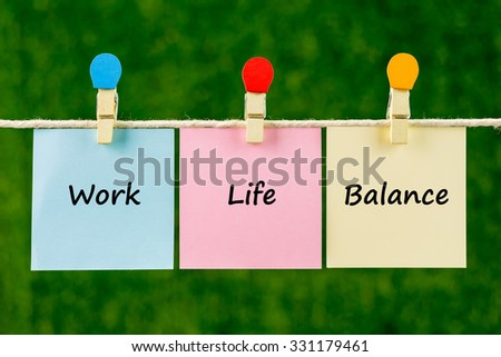 Words of Work Life Balance on sticky color papers hanging by a rope against blurred green background.