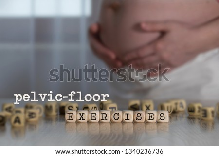 Words PELVIC-FLOOR EXERCISES composed of wooden letters. Pregnant woman in the background