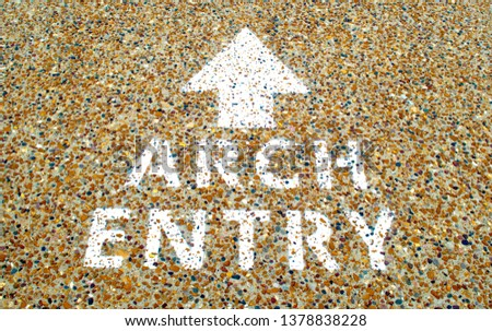 words saying Arch Entry with an arrow painted in white on a colorful pebble sidewalk