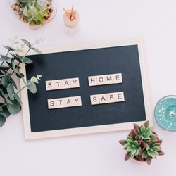 Words stay home, stay safe made of wooden blocks, concept of self quarantine at home as preventative measure against virus outbreak. Flat lay with inspiration quote, staying at home during pandemic