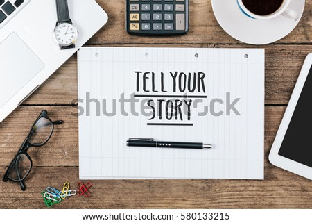 words tell your story on notebook, Office desk with electronic devices, computer and paper, wood table from above, concept image for blog title or header image. #580133215
