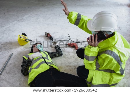Work accidents of worker in workplace at construction site area and Unconscious with colleague motion and call to the safety officer for rescue and Life-saving. Selection focus on an Injured person. Stockfoto ©