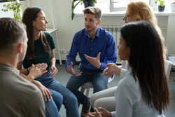 Work addict people talking on group therapy meeting, sitting in circle, discussing addiction, mental health problems. Counselor speaking, giving support and advice to team for successful recovery