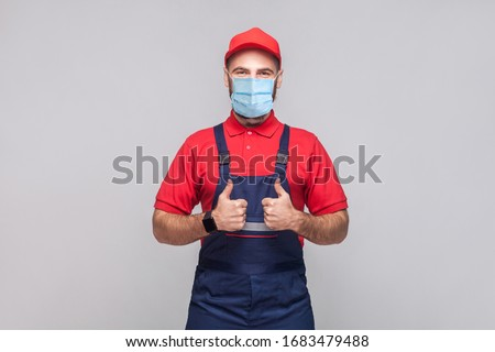 Work are done! Portrait of young man with surgical medical mask in blue overall, red t-shirt , cap, standing and showing thumps up and looking at camera. Grey background, indoor studio shot isolated.