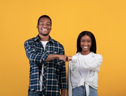 Work as team, agree to do, partnership and collaboration. Young teen happy african american couple give fist bump, agree to bring plan to life, isolated on yellow background, studio shot, free space
