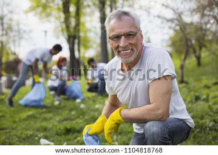 Work as volunteer. Experienced senior volunteer holding garbage bag and staring at camera