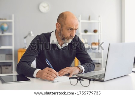 Work at home online. A senior man with a gray beard has a job in a laptop at home. Stock photo ©