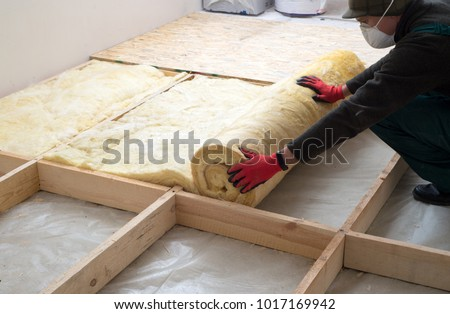 Work composed of mineral wool insulation in the floor, floor heating insulation, warm house, eco-friendly insulation, a builder at work