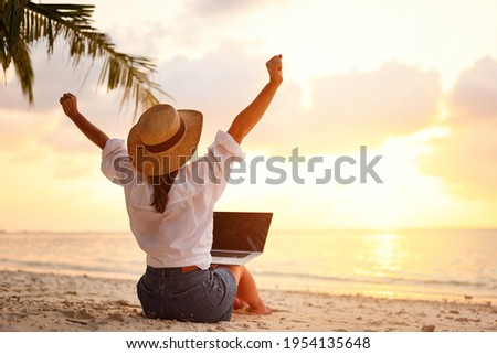 Work from anywhere. Rear view of young woman, female freelancer in straw hat working on laptop, keeping arms raised and cellebrating success while sitting on the tropical sandy beach at sunset