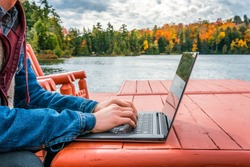 Work from anywhere - working on laptop beneath the autumn sky while on a deck near the water's edge. concept - background