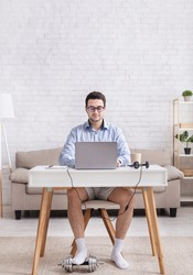 Work from home and humor. Busy, serious guy in shirt and shorts works at laptop and puts foot on dumbbell in interior of living room, free space