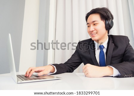 Work from home, Asian young businessman smile wearing headphones and suit video conference call or facetime with laptop computer on desk at home office