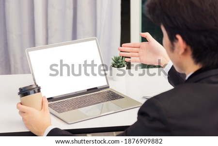 Work from home, Asian young businessman smile wearing suit video conference call or facetime by laptop computer raise his hand to explain to teammates on desk at home office