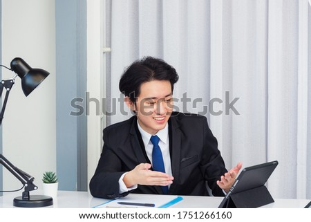 Work from home, Asian young businessman video conference call or facetime he smiling looking to tablet sitting on desk using smart tablet computer raise hand and explain to colleagues at home office
