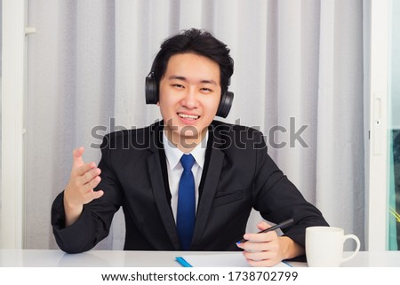 Work from home, Asian young businessman wear suit video conference call or facetime he smiling sitting on desk wearing headphones and raise his hand to explain the job he looking to camera