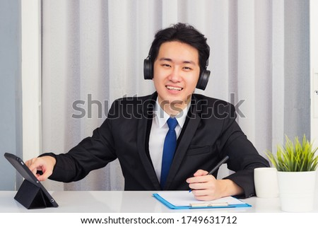 Work from home, Asian young businessman wear suit video conference call or facetime he smiling sitting on desk touch smart digital tablet computer and write paper notebook information at home office