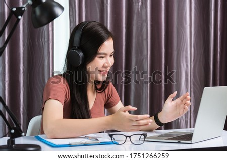 Work from home, Asian young businesswoman smile wearing headphones video conference call or facetime by laptop computer her raise his hand to explain to teammates on desk at home office