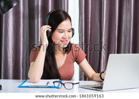 Work from home, Asian young businesswoman smile wearing headphones video conference call or facetime by laptop computer meeting with team on desk at home office